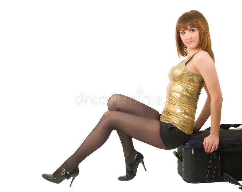 Piękny miedzianowłosy dziewczyny obsiadanie na walizce zdjęcie stock