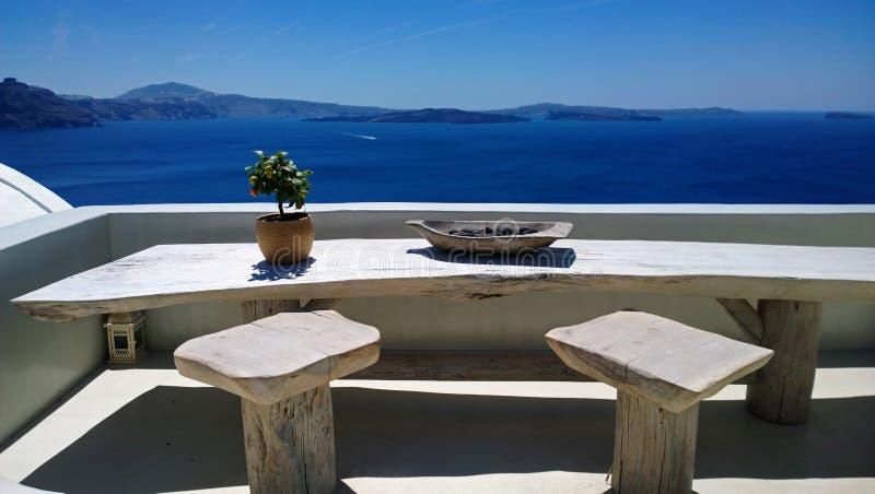 Piękny miejsce w Oia z stołem i krzesłami dla romantycznych spotkań - wielki widok jaskrawy błękitny morze obraz stock