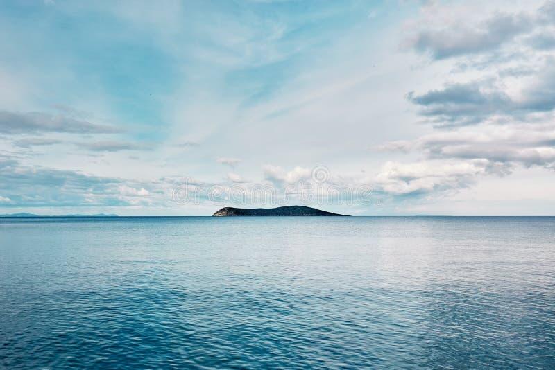 Piękny minimalistyczny natury tło błękitny morze przy wschód słońca i wyspa Wolność, orzeźwienie, spokój i przygoda, fotografia royalty free