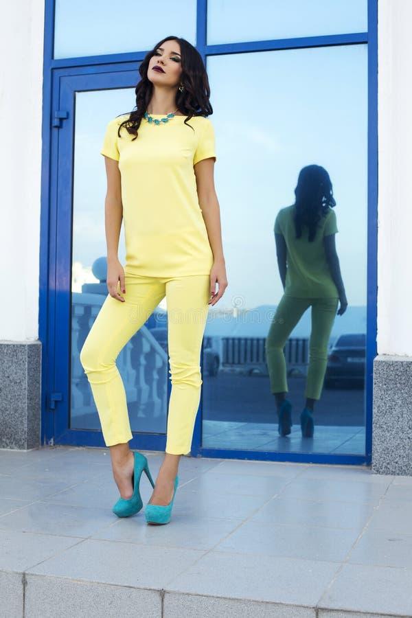 Piękny moda model jest ubranym eleganckich żółtych kostiumu i błękita buty zdjęcie royalty free