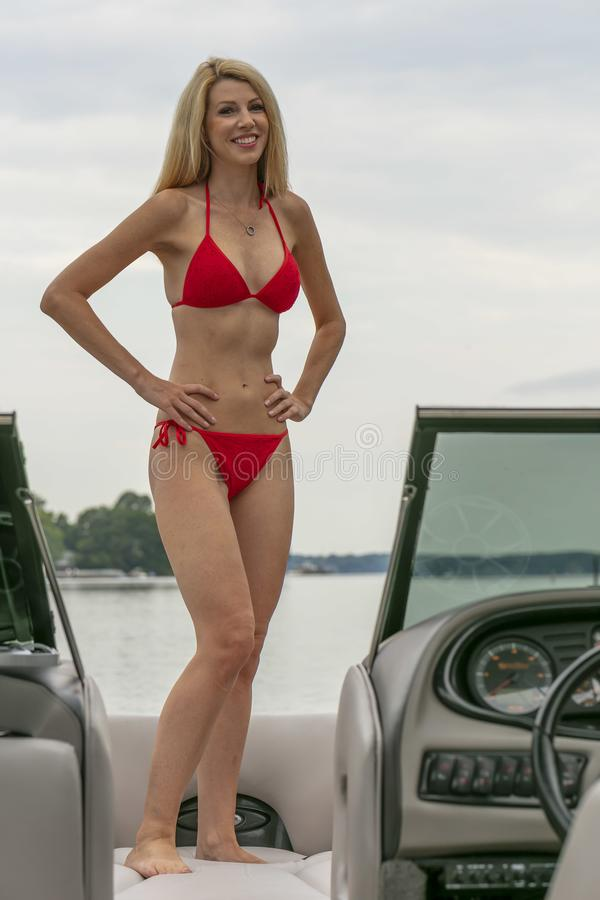 PiÄ™kny Model Bikini, Zrelaksowany Na Łodzi Przez Doki zdjęcia stock
