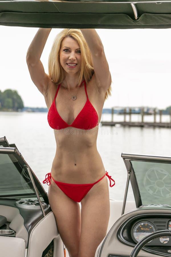 PiÄ™kny Model Bikini, Zrelaksowany Na Łodzi Przez Doki zdjęcie royalty free