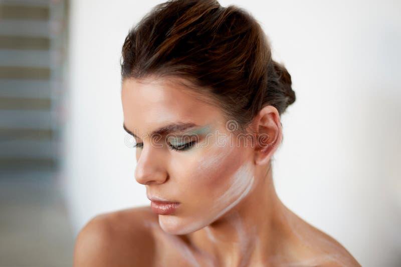 piękny model Stojaki w profilu, makeup z farb uderzeniami na twarzy kreatywna osoba obojczyki zdjęcia royalty free