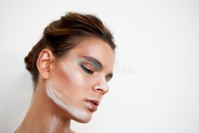 piękny model Stojaki w profilu, makeup z farb uderzeniami na twarzy kreatywna osoba obojczyki obrazy stock