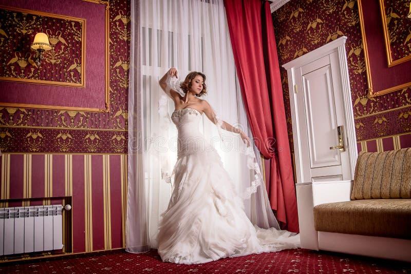 Piękny model w ślubnej sukni pozuje stać w pracownianej fotografii sesi fotografia royalty free