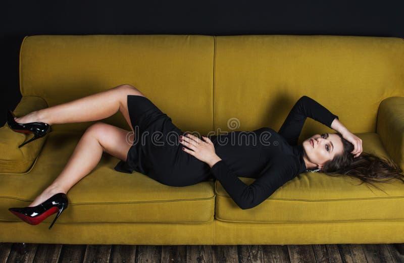 Piękny model w czerni smokingowy kłaść na kanapie obrazy royalty free
