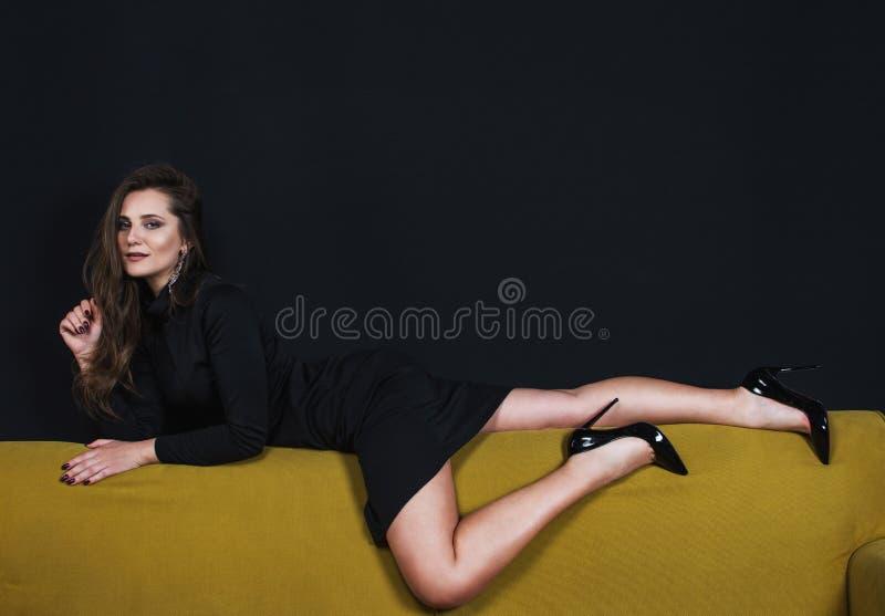 Piękny model w czerni smokingowy kłaść na kanapie zdjęcie stock