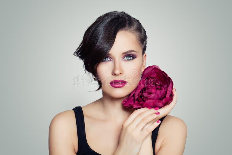 Piękny model z jaskrawym makeup i kwiatem Kobiety wiosny makeup portret fotografia royalty free