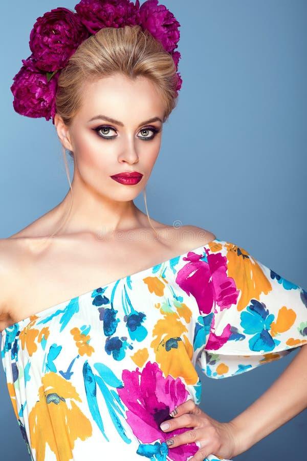 Piękny model z updo włosy i perfect jaskrawym uzupełniał będący ubranym kolorową otwartą ramię suknię z kwiecistego druku i peoni fotografia stock