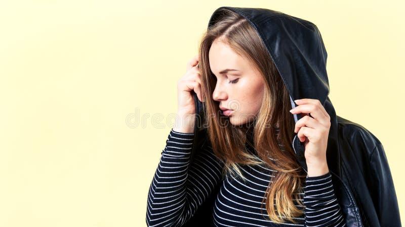 Piękny nastolatek z imbirowym włosy i piegami pozuje dla moda portreta w czarnej skórzanej kurtce, pastelowych kolorów tło obrazy royalty free
