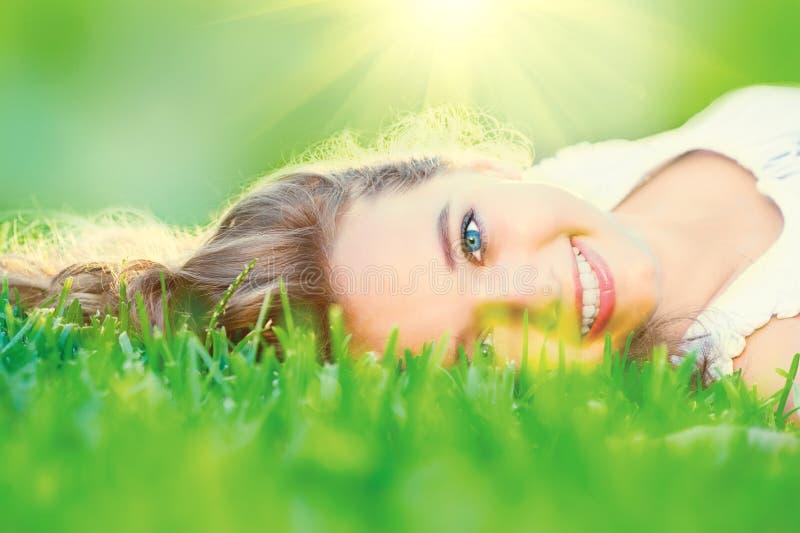 Piękny nastoletniej dziewczyny lying on the beach na zielonej trawie zdjęcia royalty free