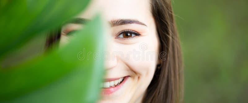 Piękny naturalny młodej kobiety zbliżenie za dużym monstera liściem z zielonym tłem w drewnach zdjęcia royalty free