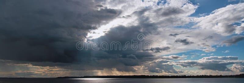 Piękny niebo nad rzeką z światła słonecznego łamaniem przez burz chmur zdjęcie royalty free