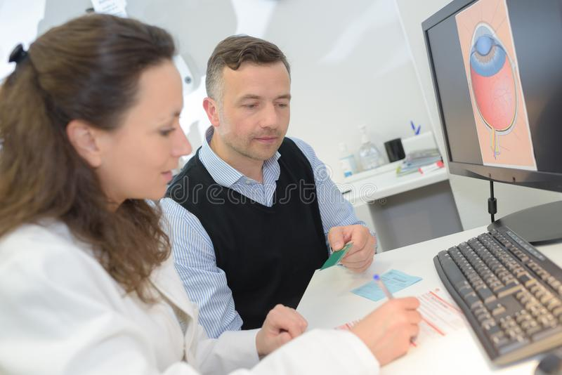 Piękny optometrist używa komputer w okulistyki klinice zdjęcie royalty free
