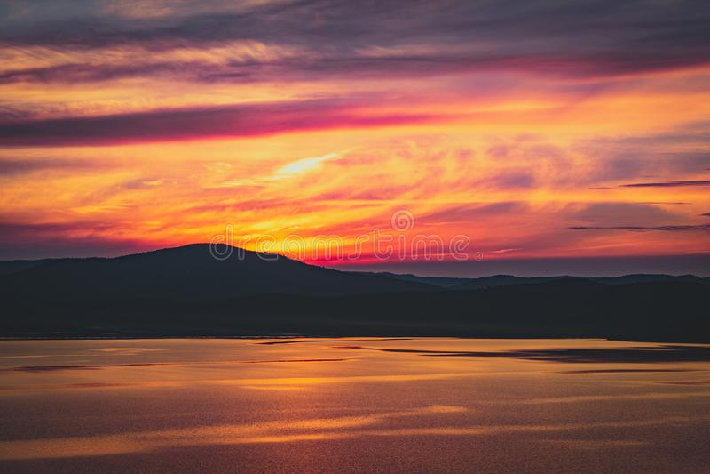Piękny płonący chmurny zmierzch przy jeziorem z słońcem iść za górami zdjęcia stock