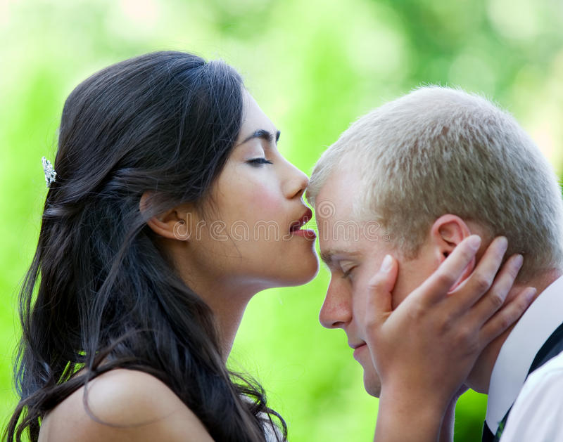 Piękny panny młodej całowania fornal na czole zdjęcia royalty free