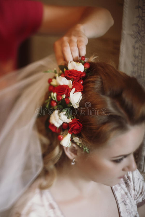 Piękny panny młodej kładzenie na kwiecistym kierowniczym wianku, stylista robi hai zdjęcia royalty free