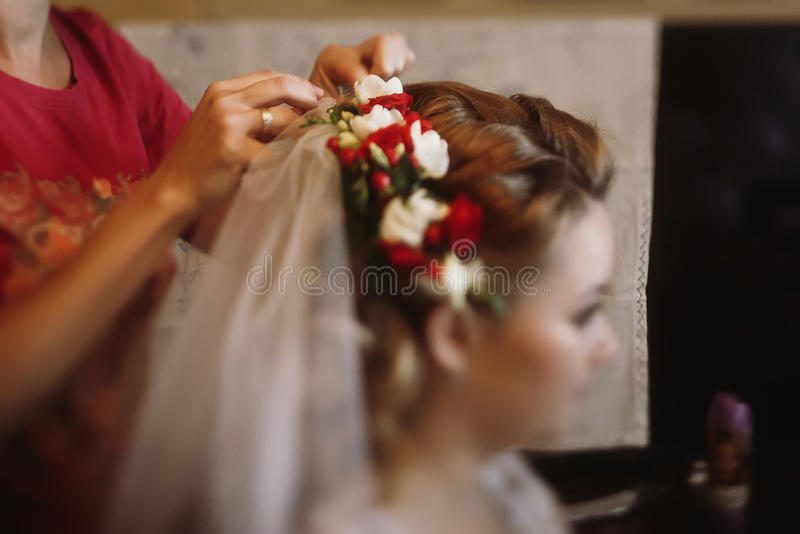 Piękny panny młodej kładzenie na kwiecistym kierowniczym wianku, stylista robi hai obrazy stock