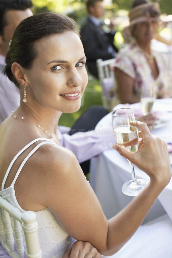 Piękny panny młodej obsiadanie Z gościami Przy ślubu stołem fotografia stock
