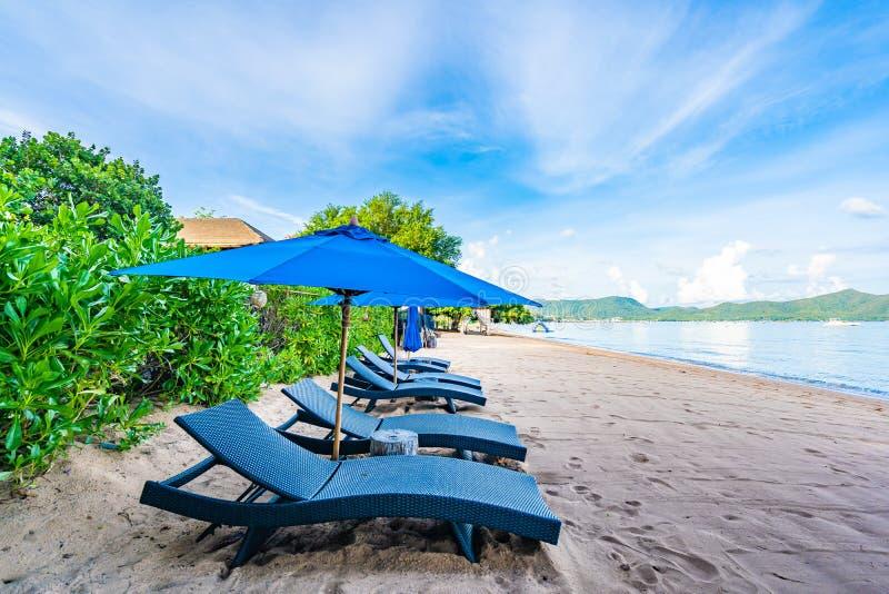 Piękny parasol, pusty łóżkowy krzesło na tropikalnej plaży i morze z bielem chmurniejemy niebieskiego nieba tło zdjęcie royalty free