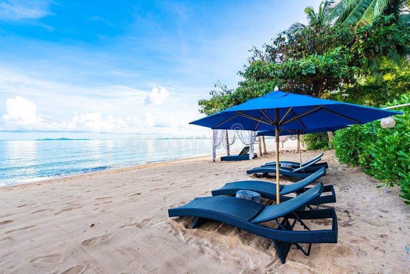 Piękny parasol, pusty łóżkowy krzesło na tropikalnej plaży i morze z bielem chmurniejemy niebieskiego nieba tło zdjęcia stock