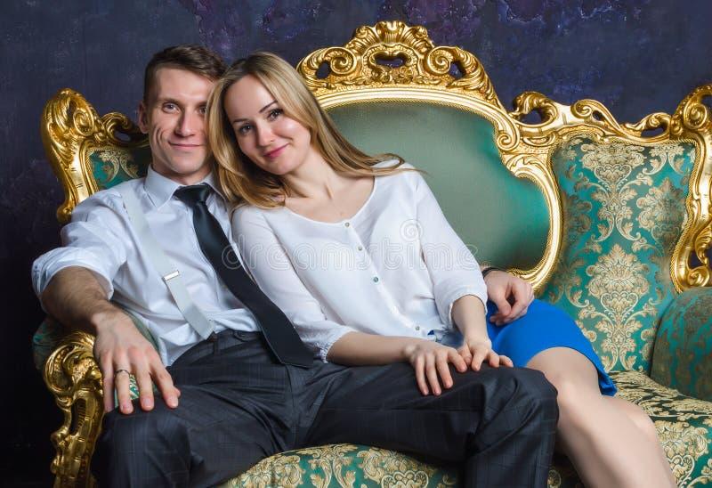 Piękny pary obsiadanie na klasycznej kanapie Dziewczyna i chłopiec na zielonej kanapie szczęśliwa mężatka pary Pomyślni ludzie w  zdjęcia royalty free
