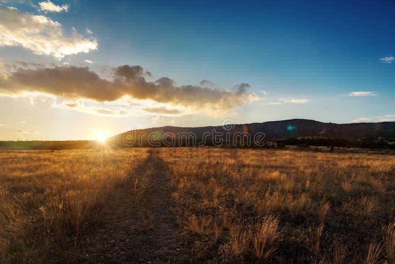 Piękny pomarańczowy jesień zmierzch w suchej trawy polu z drogą Halny tło obrazy royalty free