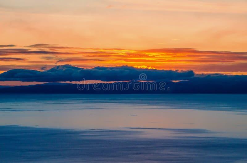 Piękny pomarańczowy zmierzch nad jeziorem z górą obrazy stock