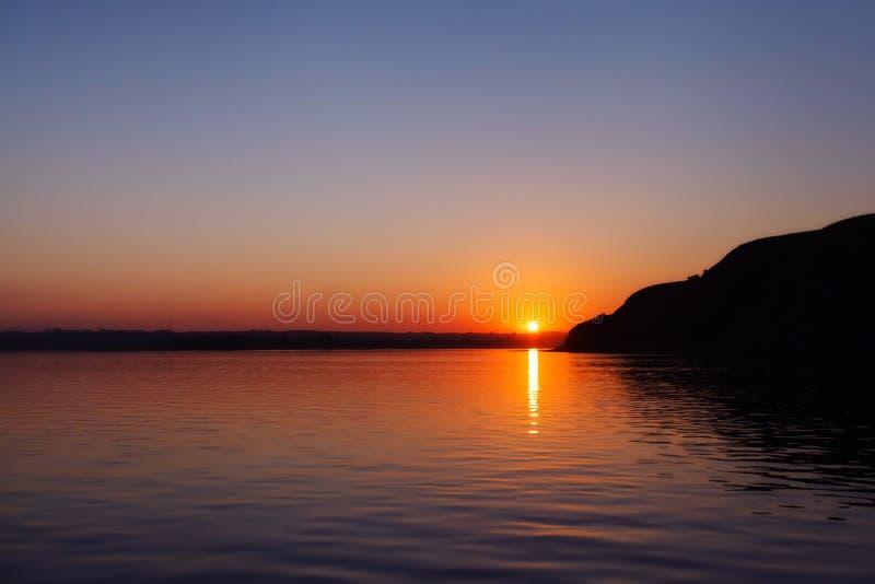 Piękny pomarańczowy zmierzch nad rzeką z odruchem zdjęcie stock