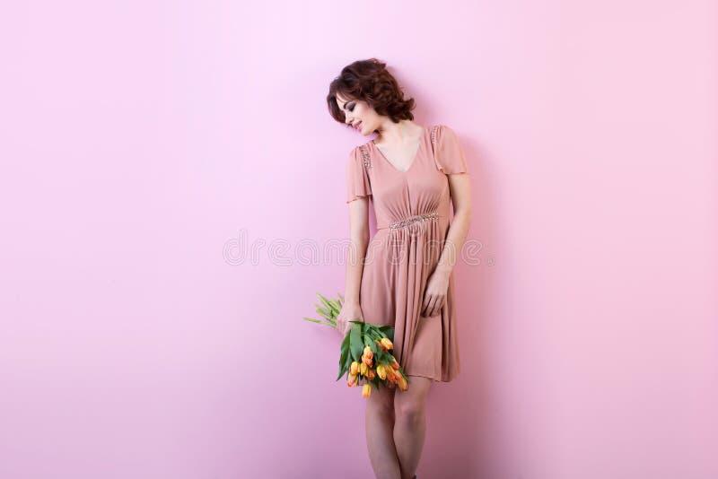 Piękny portret ładna kobieta z bukietem kwiaty nad menchiami obraz stock