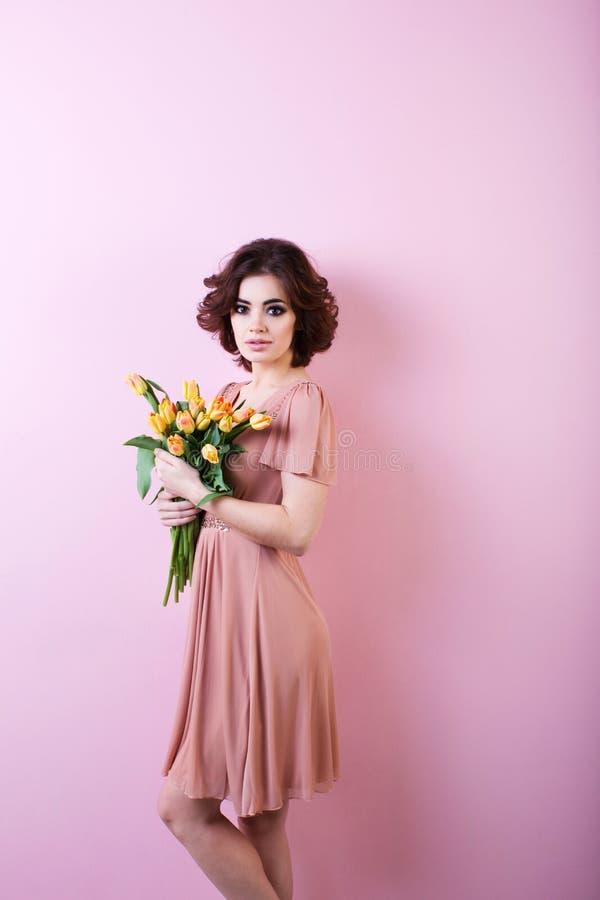 Piękny portret ładna kobieta z bukietem kwiaty nad menchiami fotografia stock
