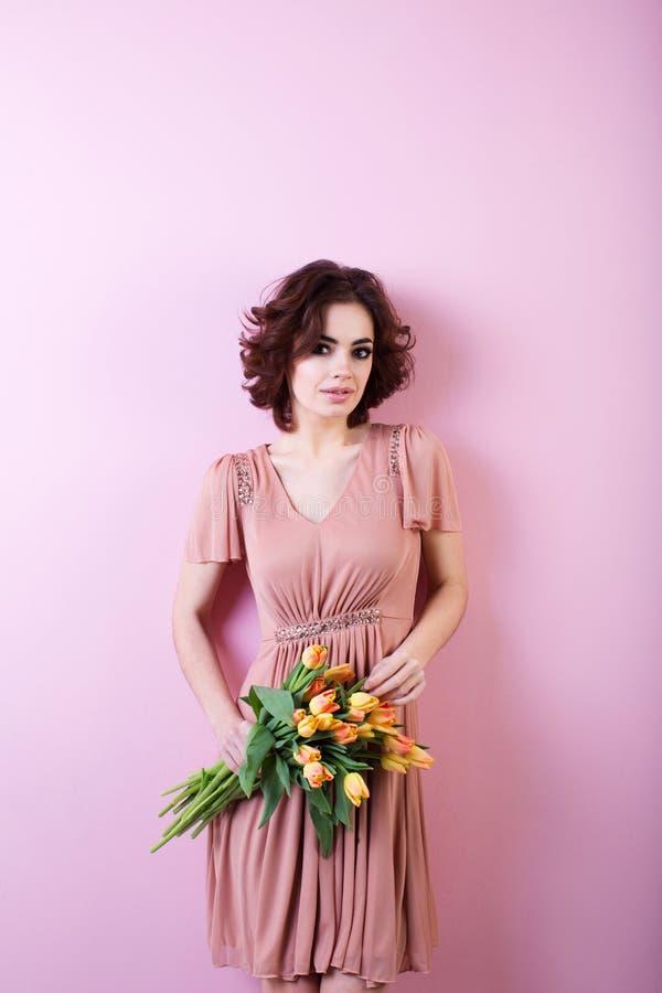 Piękny portret ładna kobieta z bukietem tulipany nad menchiami obraz stock