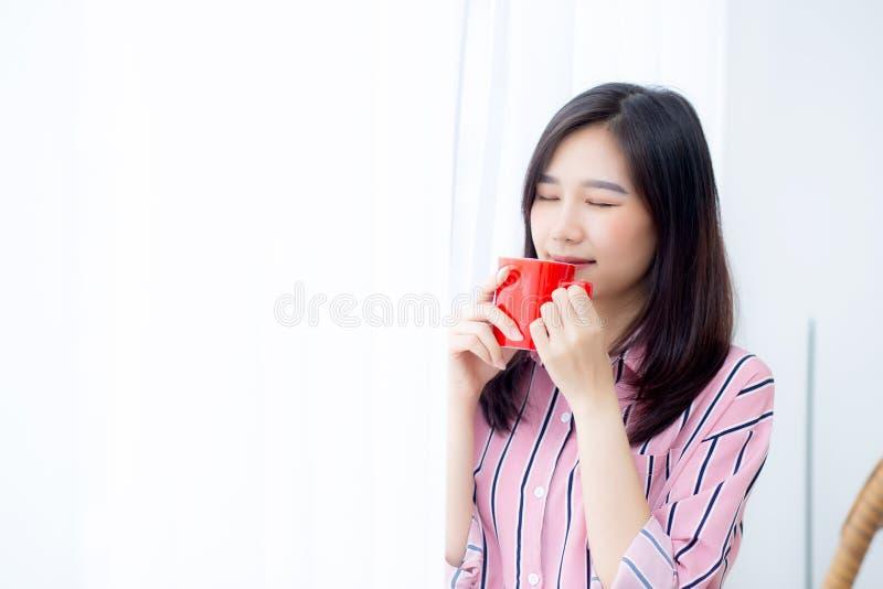 Piękny portret młoda azjatykcia kobieta z napojem filiżanka kawy trwanie zasłony nadokienny tło w sypialni, dziewczyna relaksuje  obraz stock