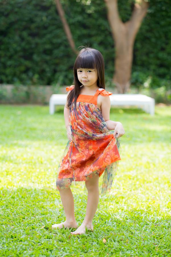 Piękny portret małej dziewczynki azjata uśmiechnięta pozycja na zielonej trawie przy parkiem zdjęcia royalty free