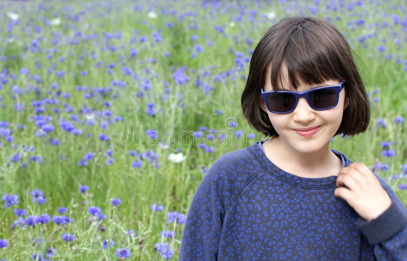 Piękny portret nieśmiały dziecko nad zamazaną naturalną chabrową łąką fotografia royalty free