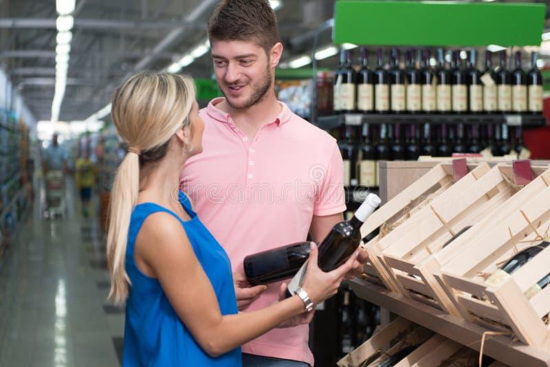 Piękny potomstwo pary zakupy Vino W supermarkecie zdjęcia royalty free