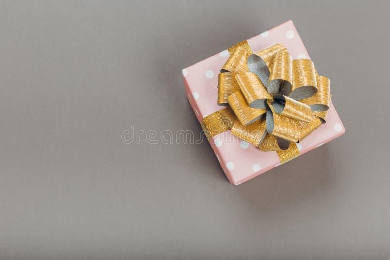 Piękny prezenta pudełko zawijający w papierze z złocistym faborkiem i łęk na szarej powierzchni Odg?rny widok obrazy royalty free
