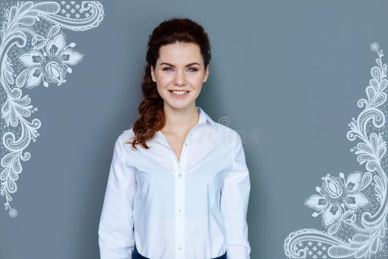 Piękny projektant uśmiecha się jej nowego wzór i pokazuje obraz royalty free