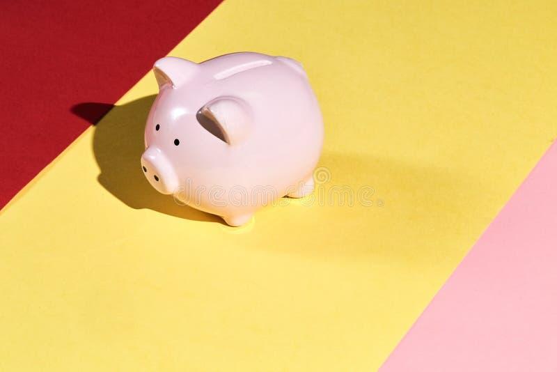 Piękny różowy prosiątko bank odizolowywający na koloru żółtego, menchii i czerwieni tle, obrazy stock