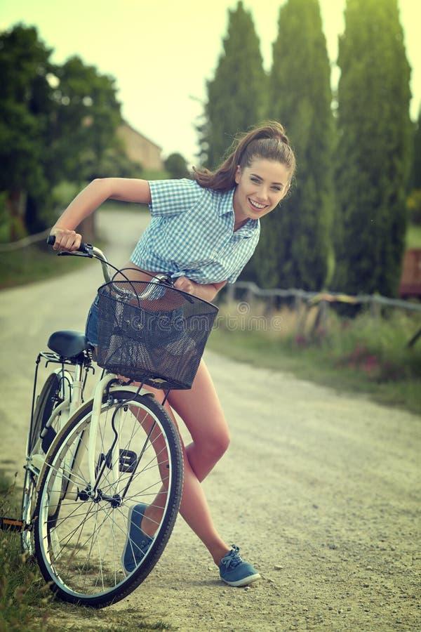 Piękny rocznik dziewczyny obsiadanie obok roweru, lato czas zdjęcie stock