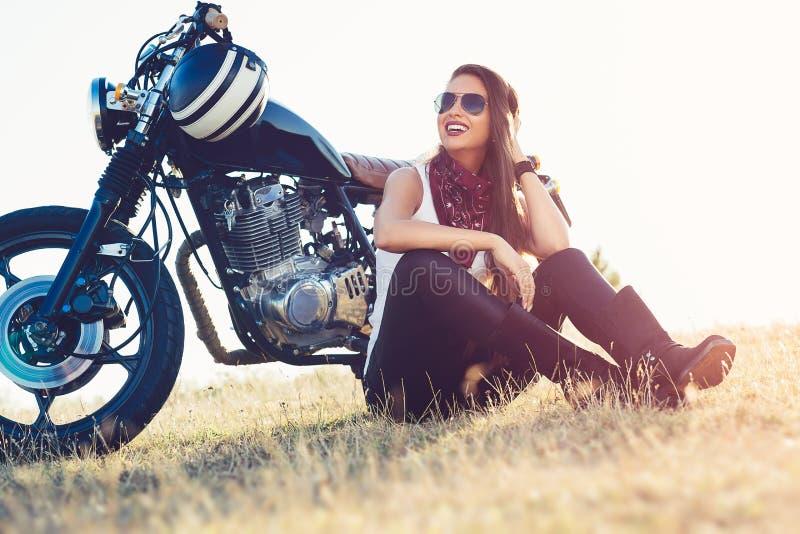 Piękny rowerzysta kobiety obsiadanie jej motocyklem na autostradzie zdjęcie royalty free