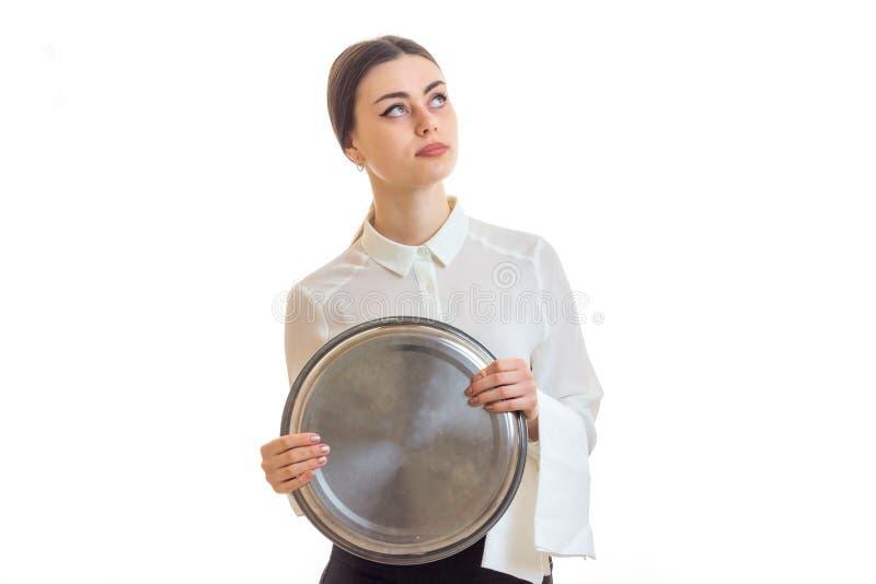 Piękny rozważny kelner trzyma wielką round tacę przyglądającego up i obraz royalty free