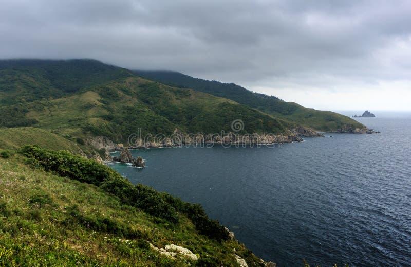 Piękny seascape - zieleni wzgórza, morze, wyspa na horyzontu und zdjęcia royalty free