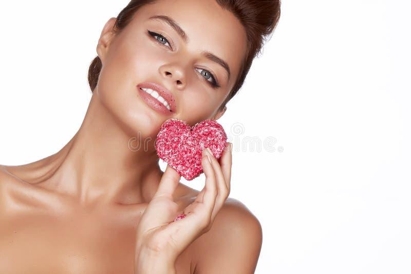 Piękny seksowny brunetki kobiety łasowania torta kształt serce na białym tle, zdrowy jedzenie, smakowity, organicznie, romantyczn obrazy royalty free
