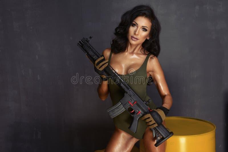 Piękny seksowny brunetki kobiety mienia pistolecik fotografia stock