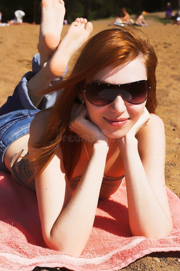 Piękny seksowny czerwony womani kłaść na morze plaży obraz stock