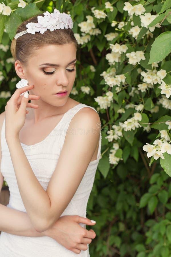 Piękny seksowny delikatny dziewczyna fornal blisko kwiatonośnego drzewa jaśmin w białej sukni z tiarą i kolczykami w postaci kwia fotografia royalty free