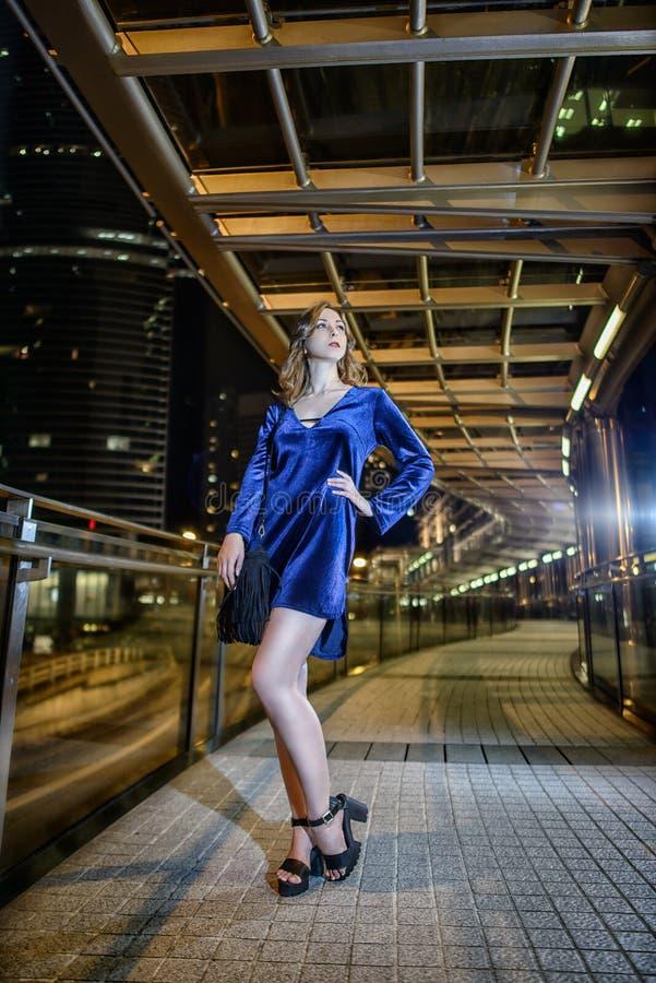 Piękny seksowny dziewczyny brązu włosy, długie chuderlawe nogi, mody błękita skrótu aksamita stylowa suknia z czarną małą torbą w zdjęcia stock