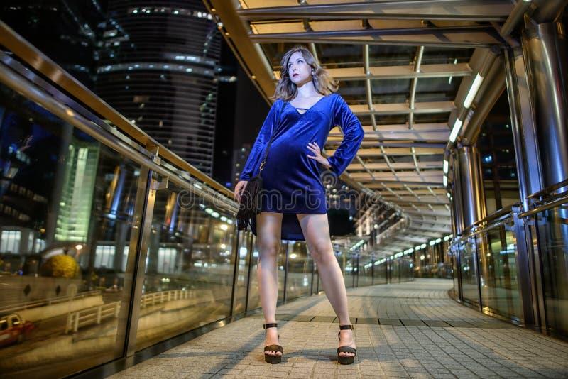 Piękny seksowny dziewczyny brązu włosy, długie chuderlawe nogi, mody błękita skrótu aksamita stylowa suknia z czarną małą torbą w zdjęcie royalty free