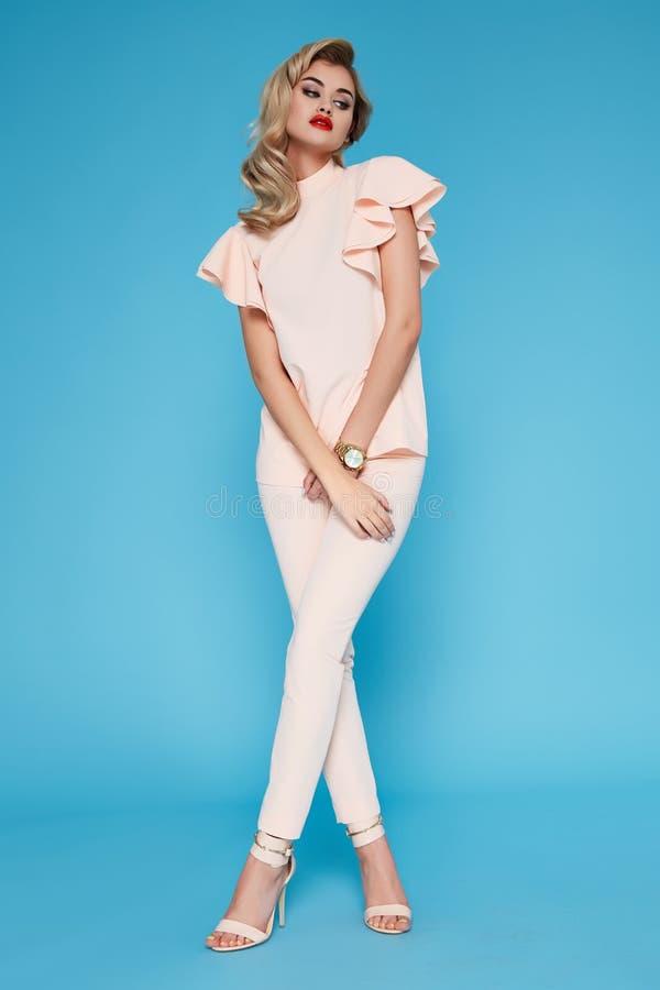 Piękny seksowny młody biznesowej kobiety blondyn z wieczór makijażem jest ubranym smokingowego kostiumu wierzchołek heeled buta b fotografia stock
